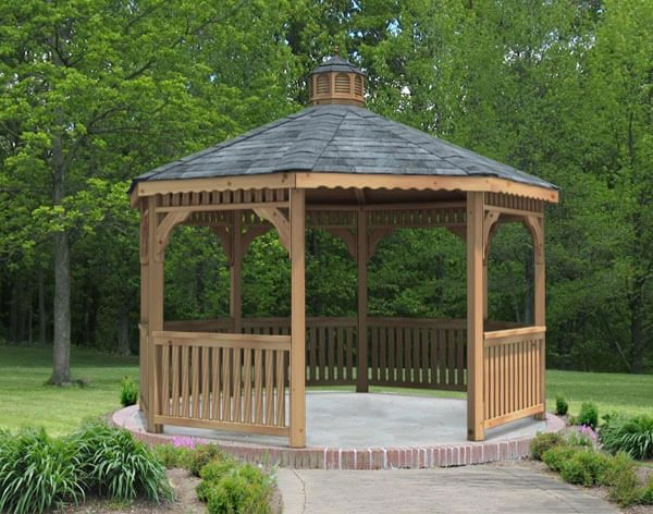 Octagonal gazebos keep that classic shape. This wooden example is sitting on a concrete pad rimmed by brick pavers.