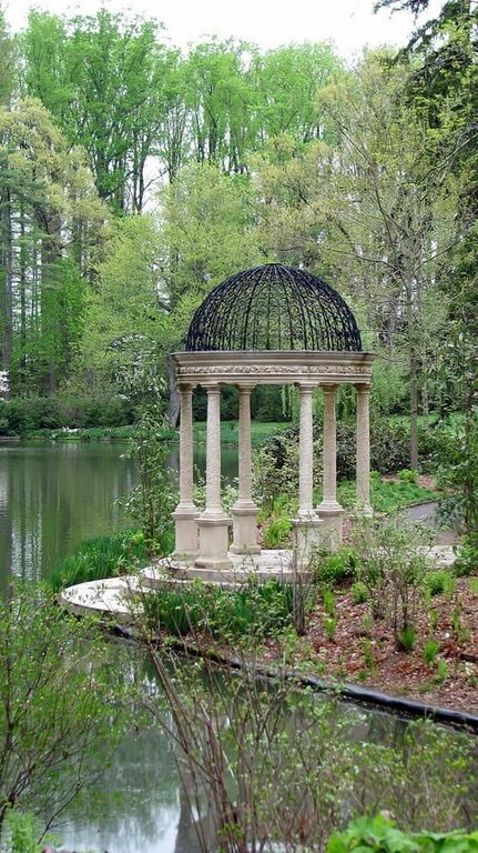 This is a great example of a round gazebo. The top is wrought iron and incredibly ornate. This is a small gazebo, but it's perfect for sitting or just for admiring from far away.