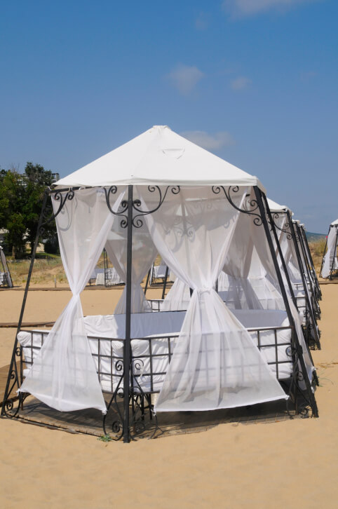 An aluminum gazebo with a canopy top and cushions formed to make a cozy bed-like structure. This gazebo is a luxurious way to relax on the beach and beat the summer heat.