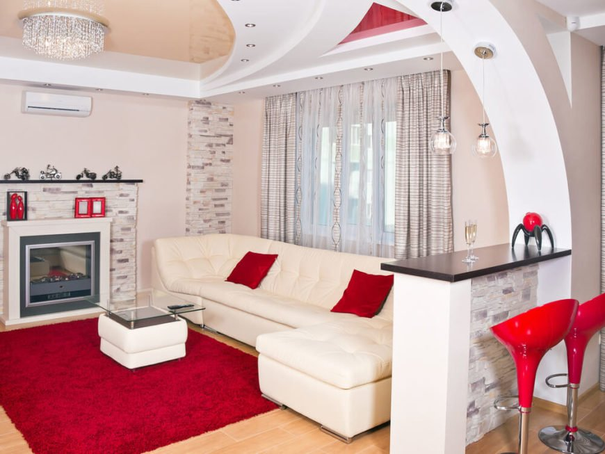 Your ceiling design is really only limited by the scope of your imagination. This modern living room has an incredible glossy ceiling design with colors abound. In the center is a low profile but glittery chandelier.