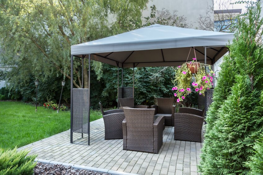 A lovely aluminum gazebo with a canvas canopy. The gazebo is placed over a brick patio and furnished with wicker chairs in a rich chocolate brown.