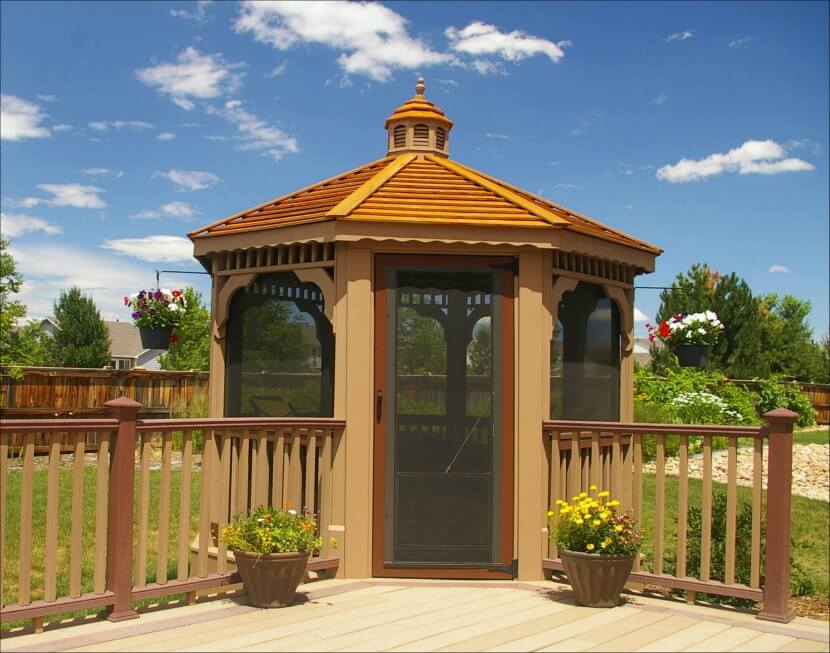 Fully enclosed wood gazebo built into the corner of a deck