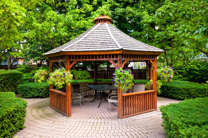 This cedar gazebo is home to a small patio dining set and is placed at the center of a garden on a brick patio surrounded by hedges and trees.