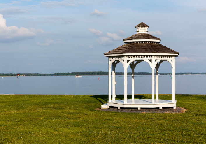 Another fantastic gazebo in white overlooking a large lake and boating area.