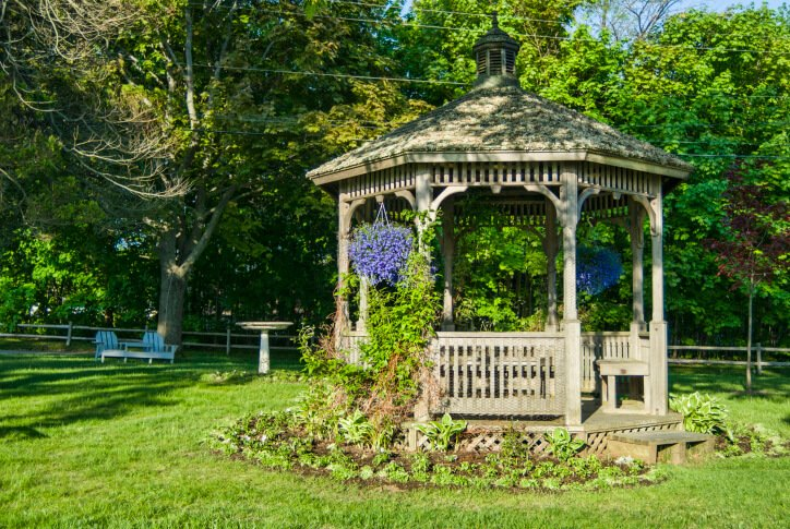 Even in the center of the yard, adding vines, hanging baskets, and planting beds around the gazebo helps create a sense of being in a secret garden.