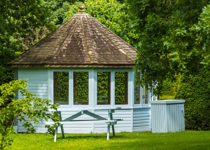 This pretty blue gazebo is fully enclosed and has a matching blue picnic table outside.