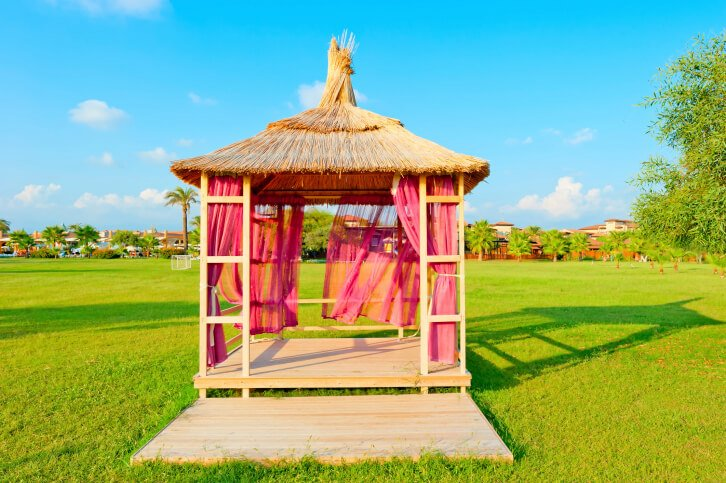 This soft-top gazebo features a rustic roof and magenta curtains.