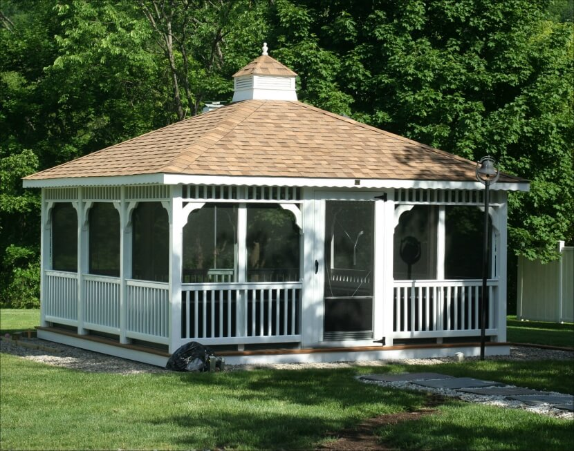An enormous screened in rectangular gazebo at the end of a gravel and flagstone pathway.