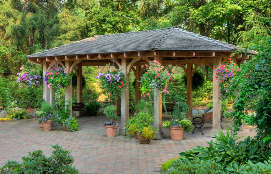 A garden pavilion style gazebo on a brick patio. While the surrounding area is lush, the gazebo stands apart. Hanging baskets and container gardens help integrate the two sections of the yard.