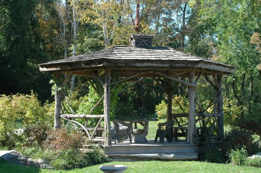 A rustic gazebo made with natural branches and logs. The structure has enough space for a dining area and a relaxation area.
