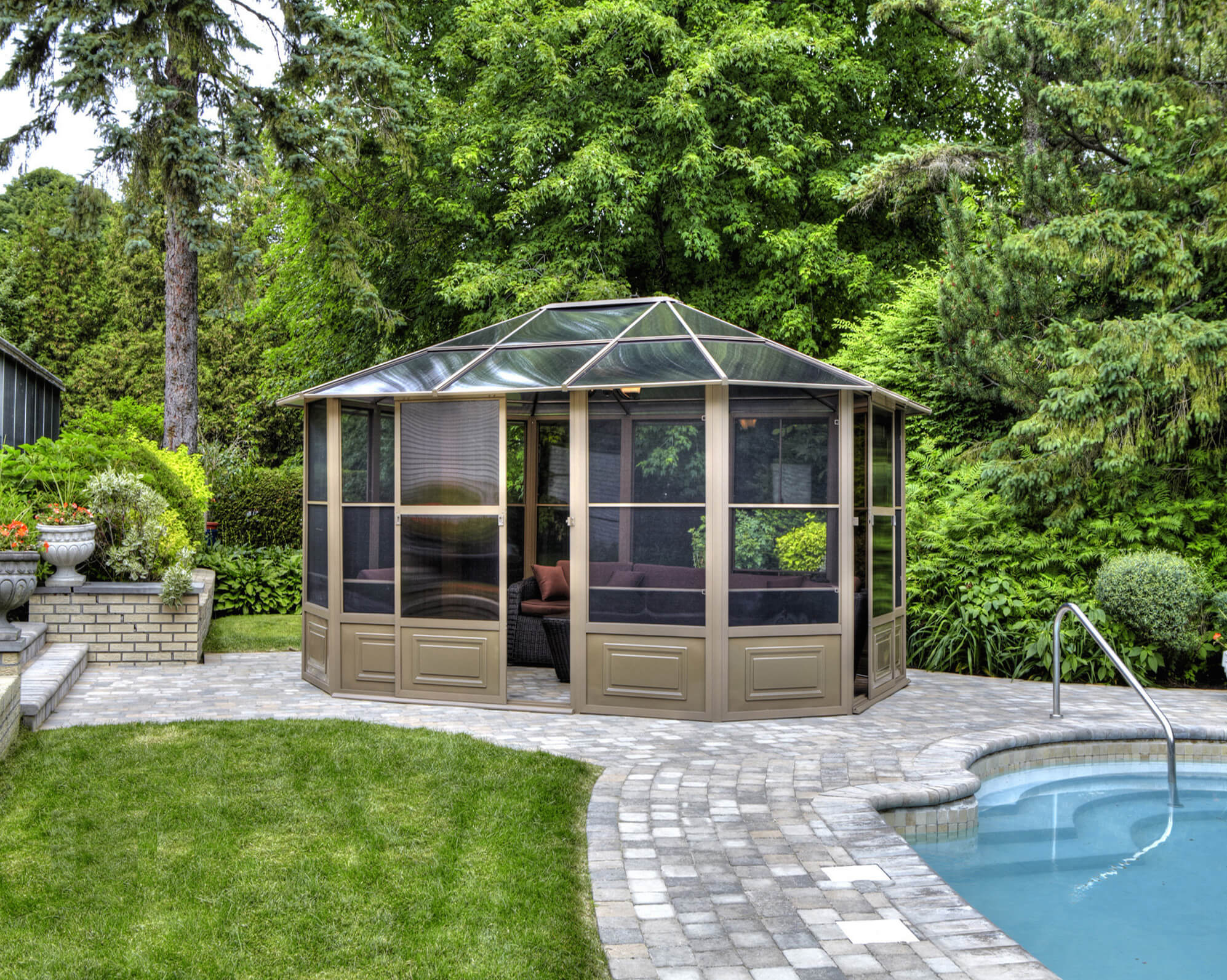 A glass roof makes an enclosed gazebo the perfect unattached solarium for a backyard. Here, it's next to a lovely pool.