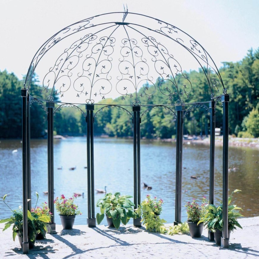 This is a simple, barebones metal gazebo on the edge of a small lake. The area is spruced up with a few small planters.