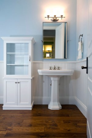 Beach powder room with light blue walls, wooden floor, pedestal sink, and wall lighting.