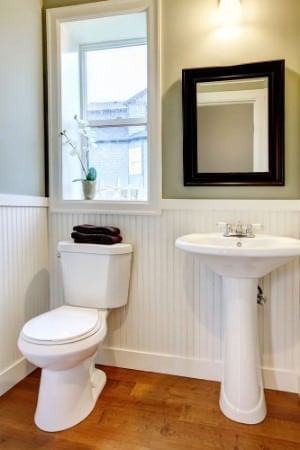 Basic powder room with white pedestal sink, wooden floor, white toilet, and wall lighting.