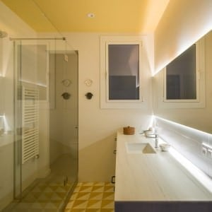 Modern powder room with undermount sink on long counter and side transparent shower area.