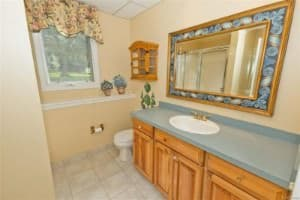 Modern powder room with single undermount sink, wooden fixtures, decorated mirror and tiled floor.