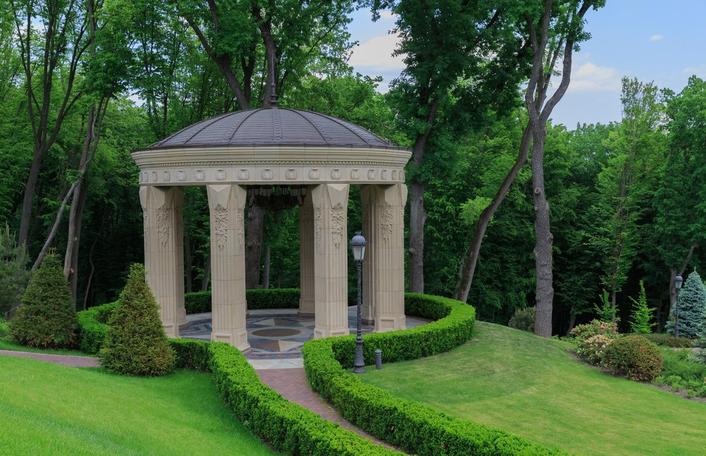 This size gazebo can fit a small wedding party. It's made of stone and erected in a lush green landscape. The natural, calming environment makes this type of gazebo perfect for weddings.