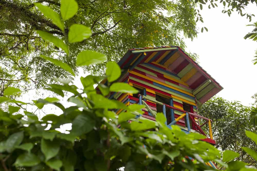 Multi-colored treehouse with gable roof and small deck.