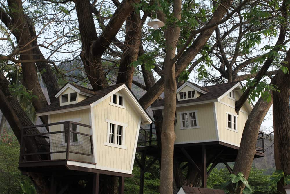 Beautiful soft yellow treehouses with small deck and windows.
