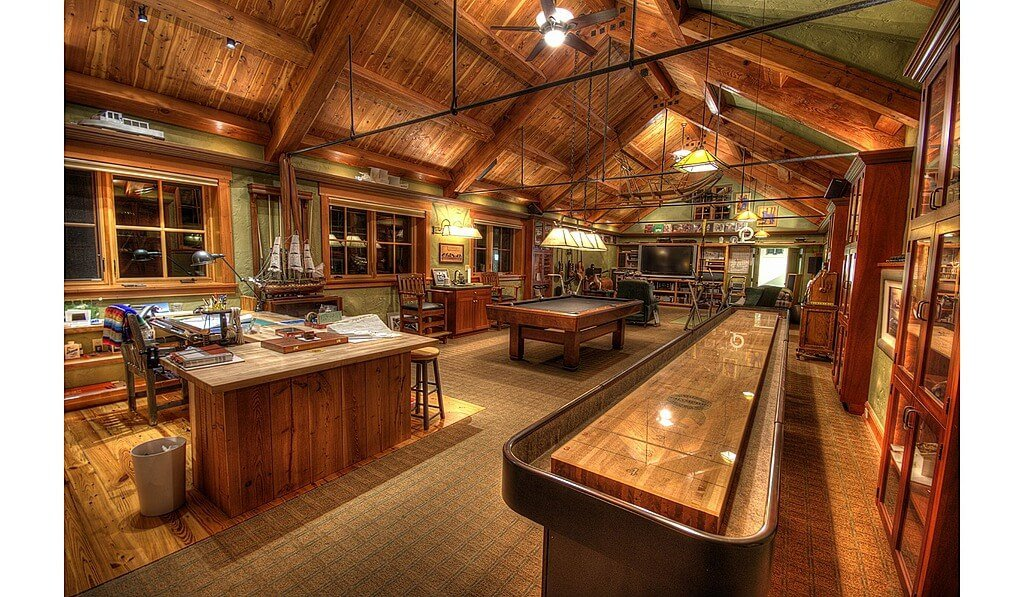 A large living area featuring a billiards pool, a living space and an office area all under the wooden vaulted ceiling with exposed beams.