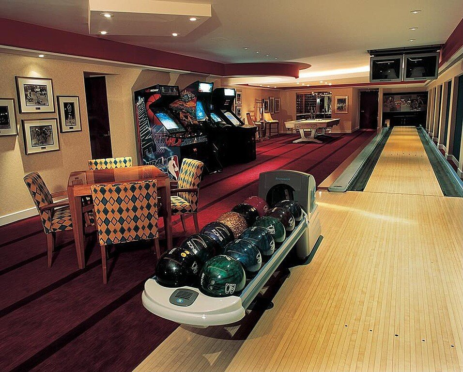 This home boasts a gaming table, multiple arcade games, a billiards pool and a bowling alley, all under the stunning ceiling with its lighting.