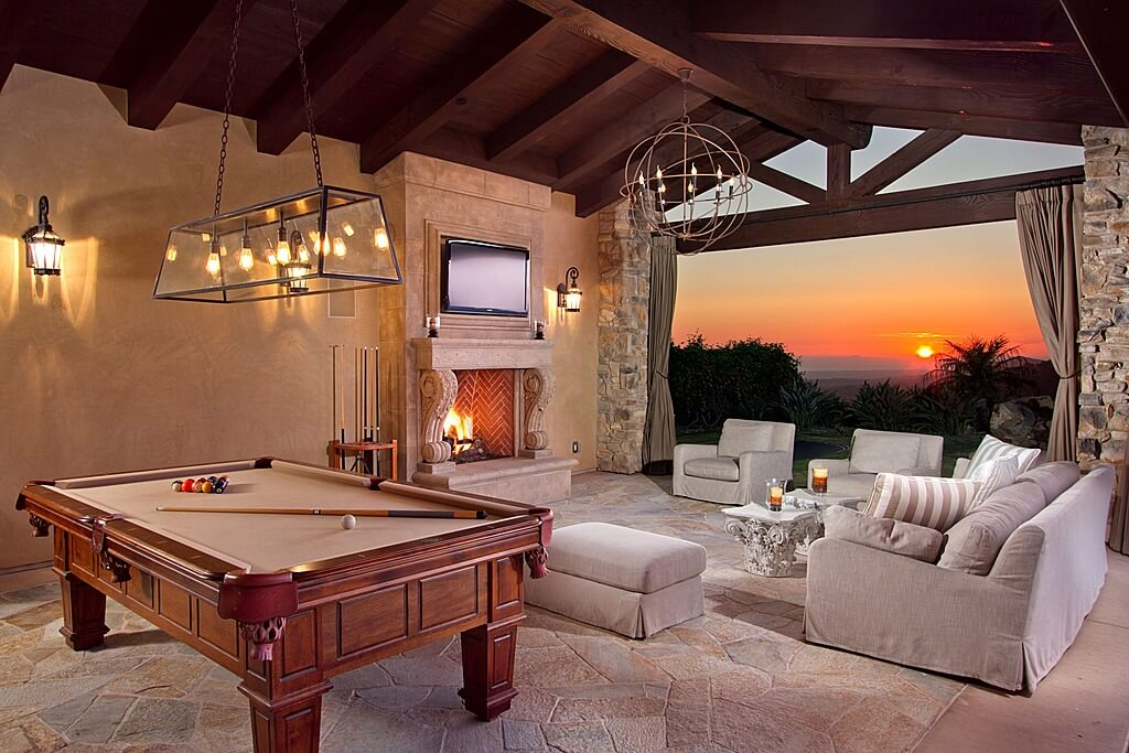 Large outdoor man cave featuring a lovely flooring and a cozy sofa set along with a stylish billiards pool, all under the vaulted ceiling lighted by very attractive ceiling and wall lights.