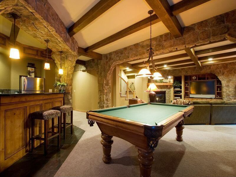 This home boasts a living room with a cozy sofa set, a billiards pool set on the carpet flooring and a bar area lighted by pendant lights.