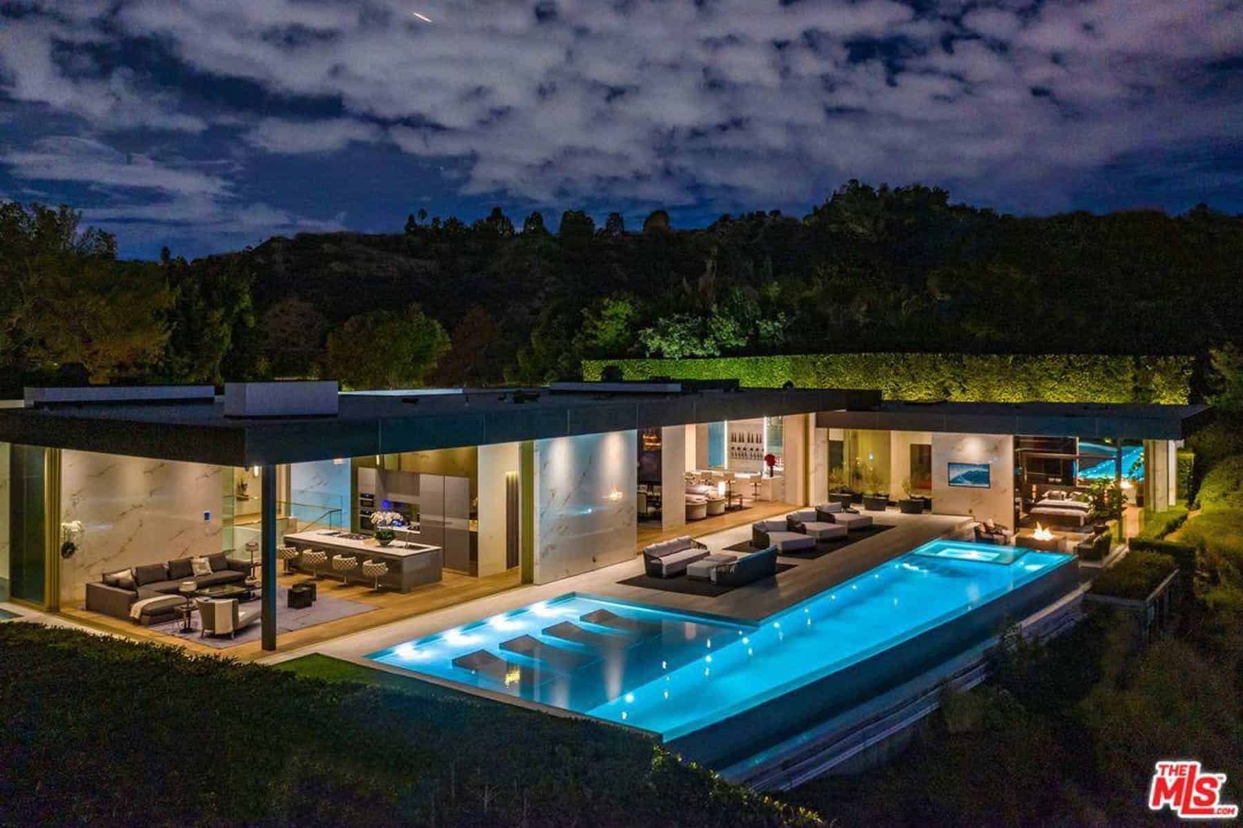 A sprawling modern mansion in Beverly Hills that has a large swimming pool with multiple sitting lounges in its side.