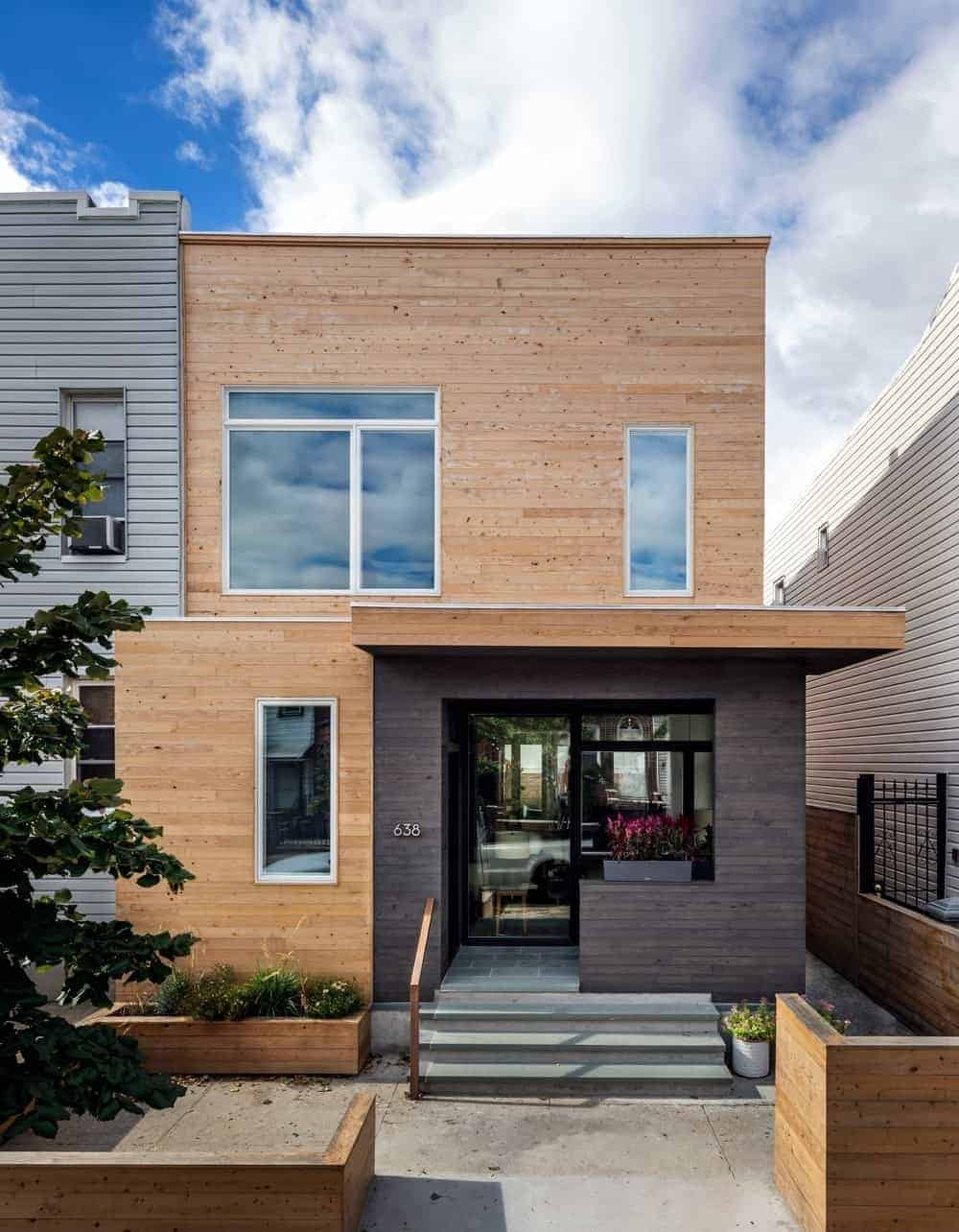 A modern house with a wooden exterior and has a stylish entry.