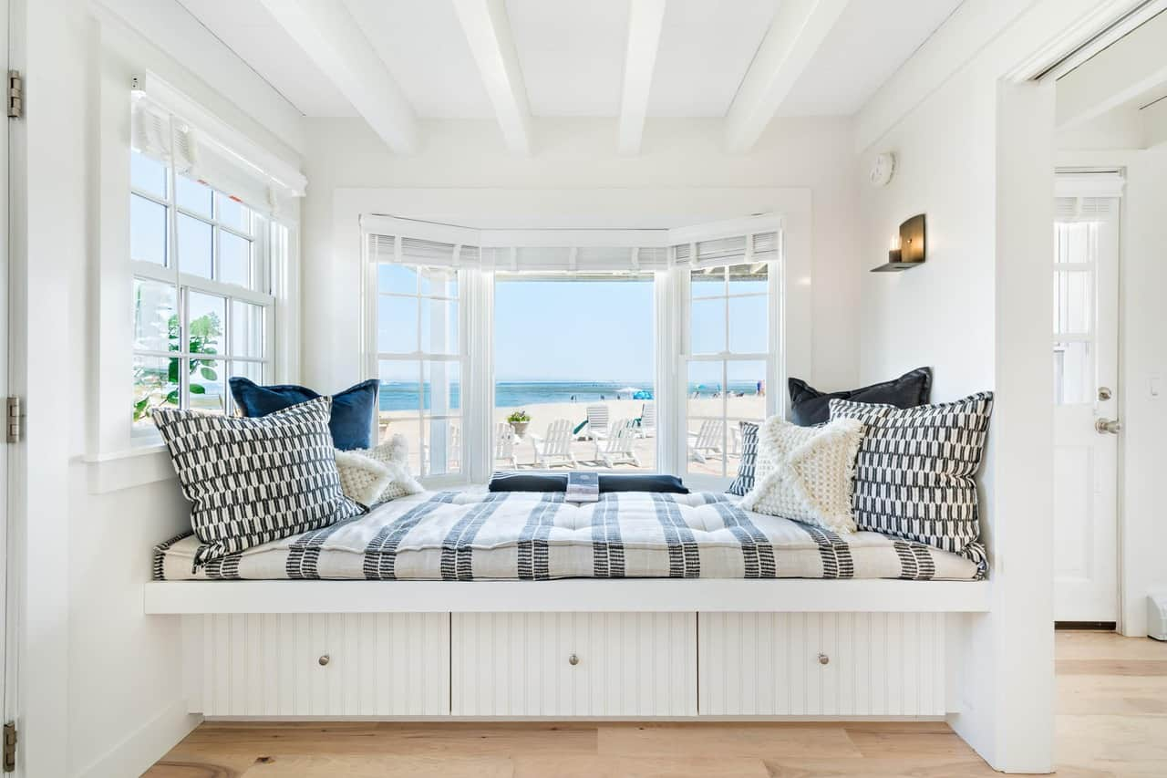 Day bed reading nook looking out on sandy beach in tiny beach house on Cape Cod
