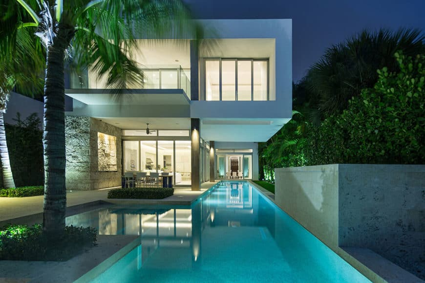 Modern white house with a custom swimming pool and an outdoor dining set.