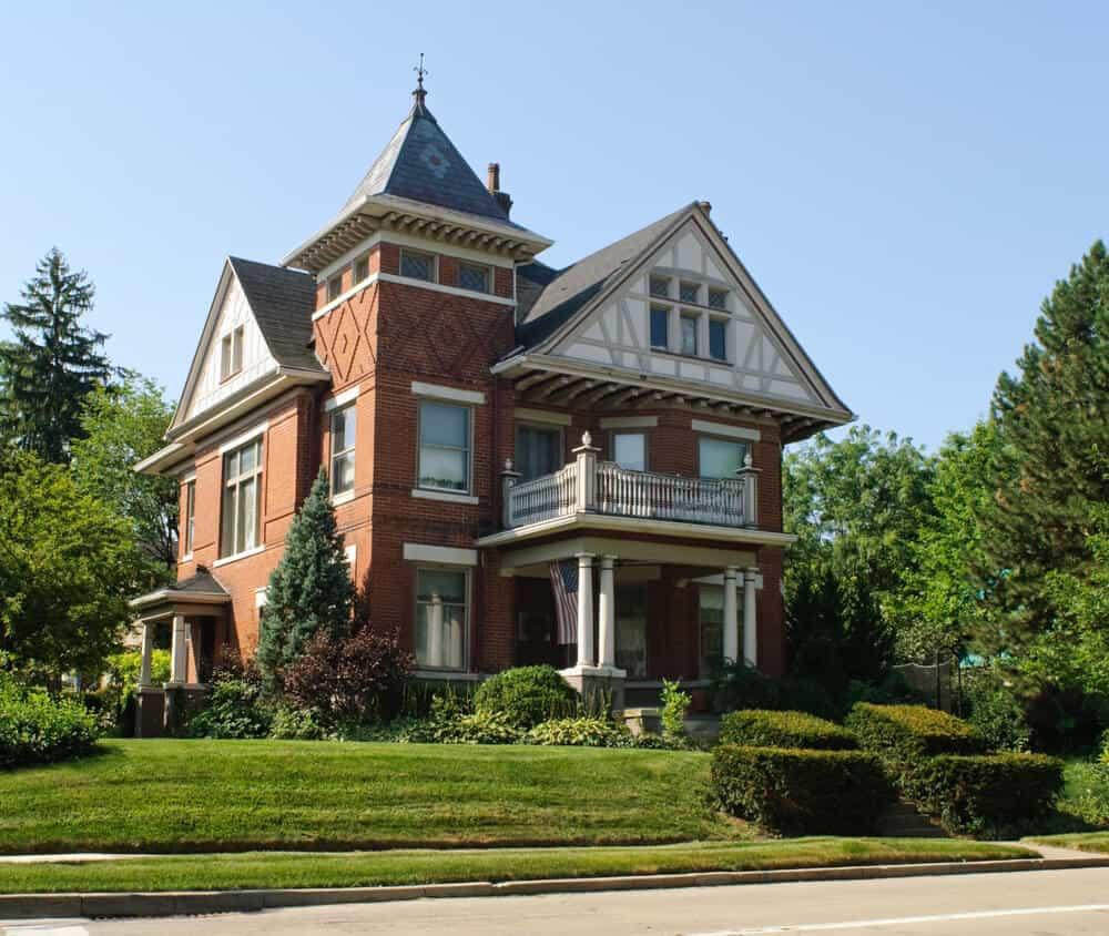 Large 3-story red brick Victorian home with white pillars in front supporting second story front deck.