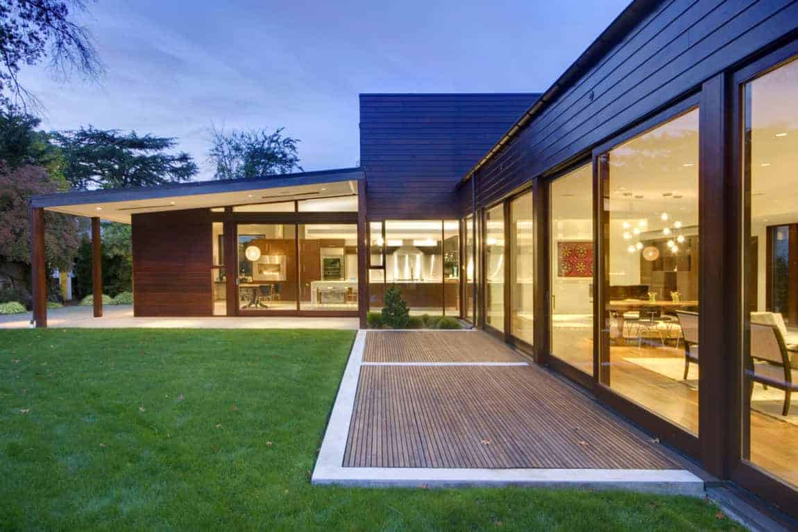 Modern house featuring a wooden exterior and a well-maintained lawn area.