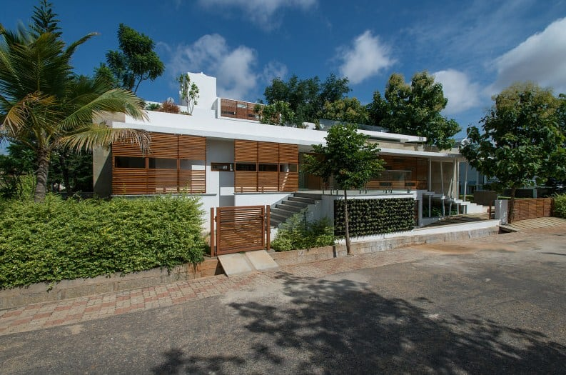 Large modern house surrounded by tall and mature trees. It has a stylish exterior as well.