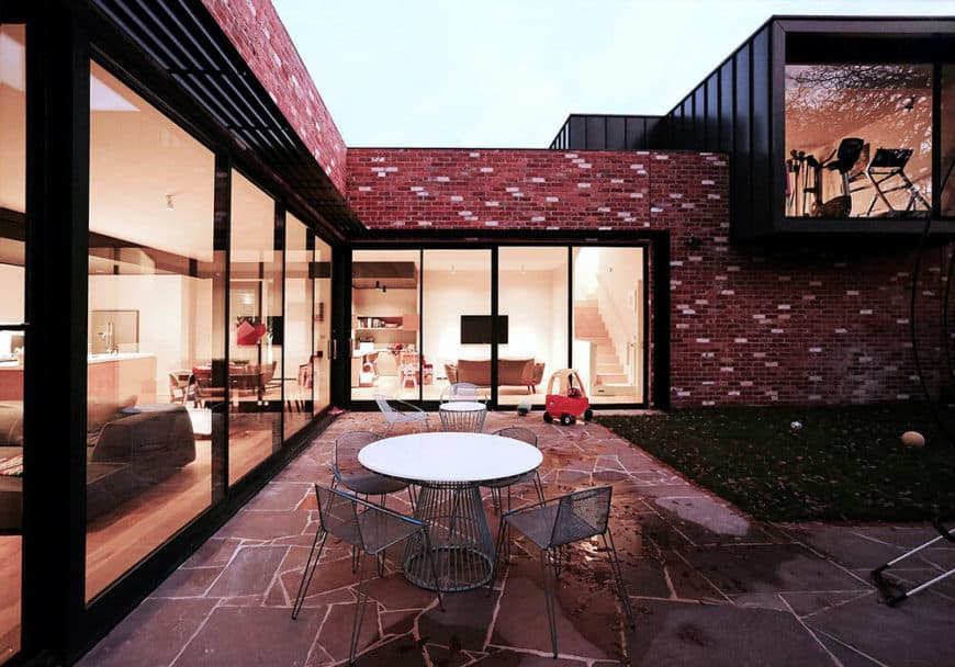 A modern house with red and black exterior along with a nice backyard.