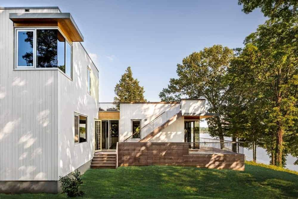 Modern white house with a spacious backyard with a well-maintained lawn area.