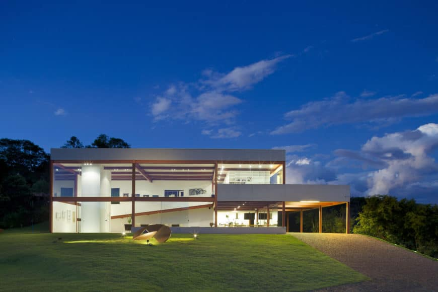 Large modern house featuring a sprawling lawn area and a beautiful driveway leading to the home's garage.