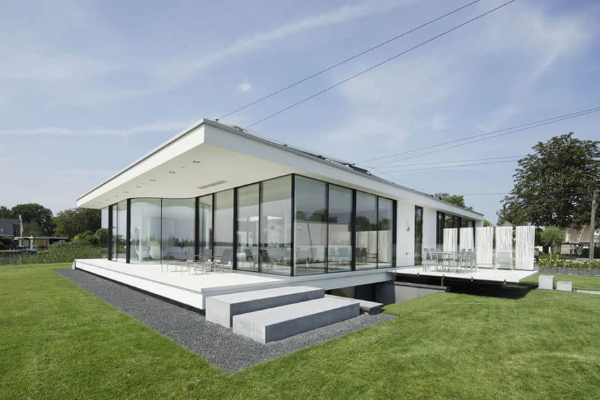 This modern white house is set on a lawn area that is well-maintained.