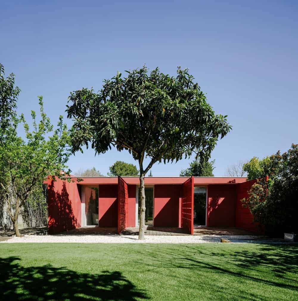 Red modern house featuring a peaceful backyard with a well-maintained lawn area.
