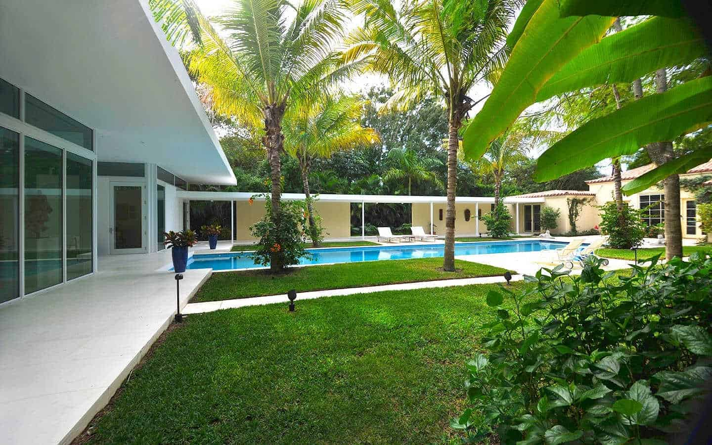 A wide modern house finished in white. It has a beautiful backyard surrounded by healthy greens.