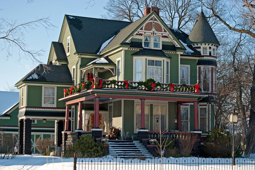Large green, black and red Victorian home with front porch and brick foundation.