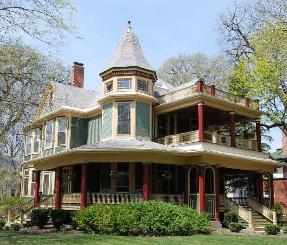 Green, red and yellow Victorian home with large round front porch and large square front deck on the second story.