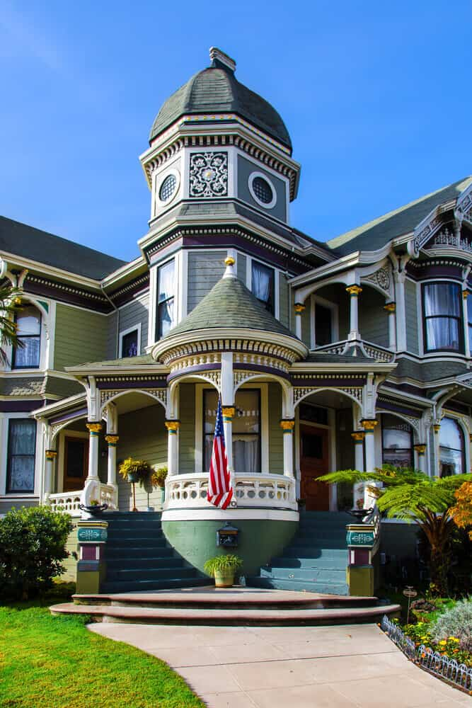 Green and white double-winged Victorian mansion in Alameda, California.