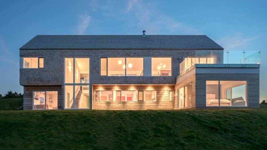 Large modern-style house with a wooden exterior. The interior boasts warm white lighting.