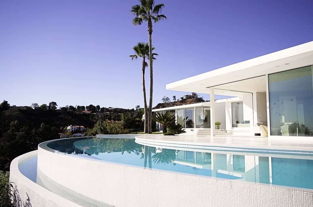 A large modern house with a white exterior. It features an infinity pool with panoramic views of the surroundings.