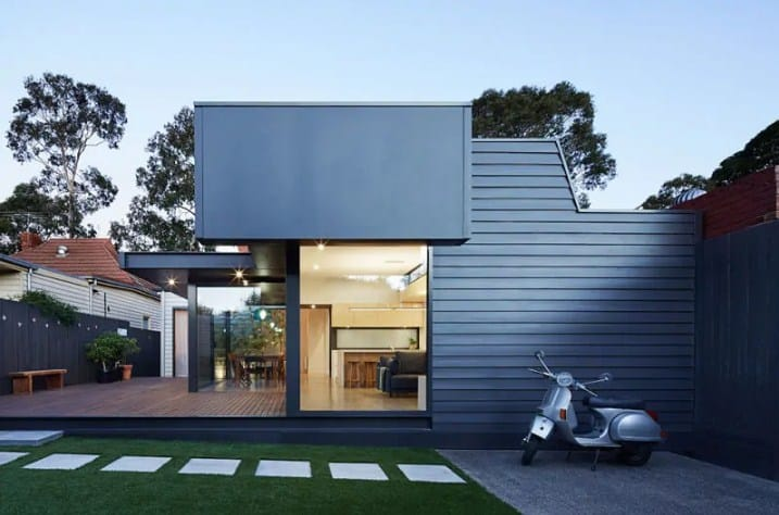 This modern house boasts a deck along with a lawn area with a simple walkway.