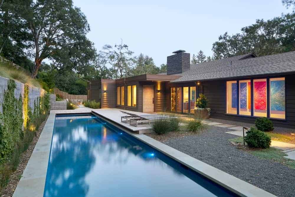 A modern home with a wooden exterior featuring a long swimming pool on the side.