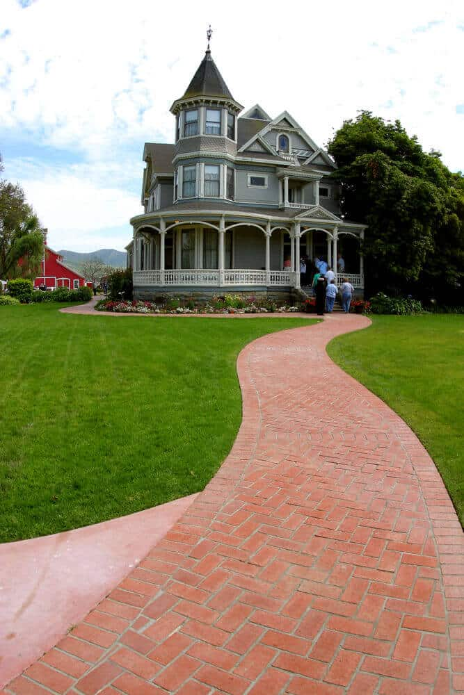 Large Victorian home on huge property with long brick front walk-way.