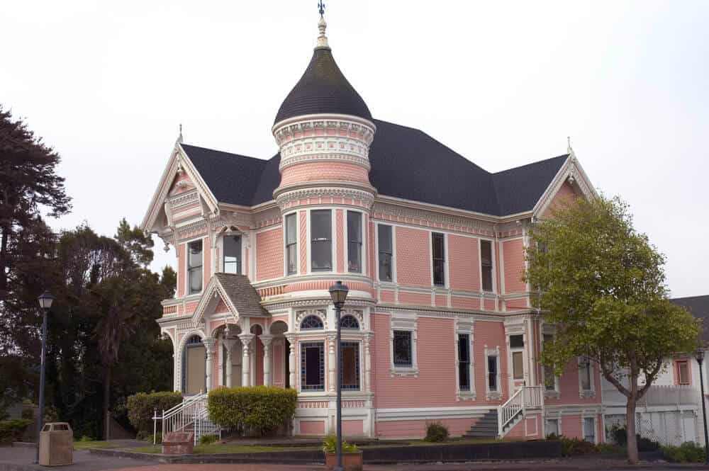 Pink Victorian mansion with white trim and dark roof with a circular town located in Eureka, California.