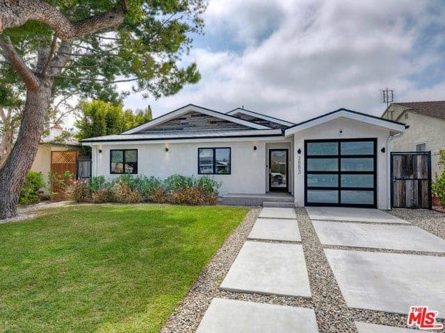 A stunning modern home with beautiful walkways and a well-maintained lawn area.